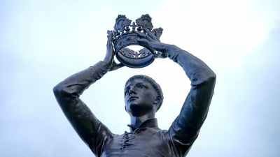 statue of king putting on his crown