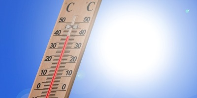 a Celsius thermometer in front of the noon sun