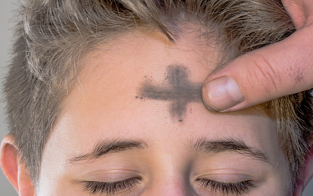 a person's forehead is marked with a cross using ash
