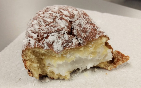 a half-eaten paczki filled with frosting