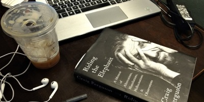 coffee shop table with craig ferguson's book Riding the Elephant next to a laptop
