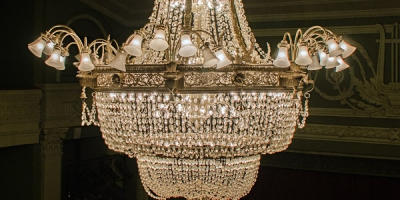 a chandelier suspended above a theater's stage and box seats