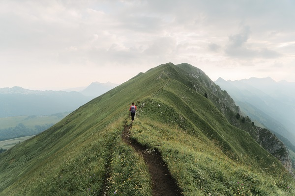 a young woman hikes along a grassy ridge in the Swiss Alps