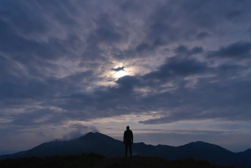 man standing alone on mountainside in dim light