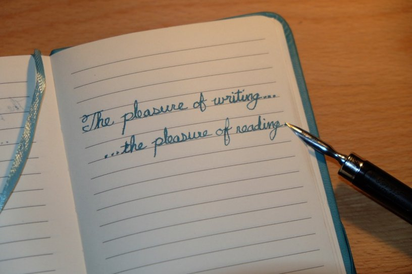 a journal with handwriting it in and an old pen