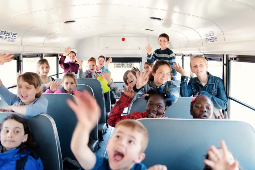 kids smiling and waving on a school bus