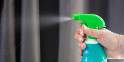image of a hand holding and spraying disinfectant from a bottle