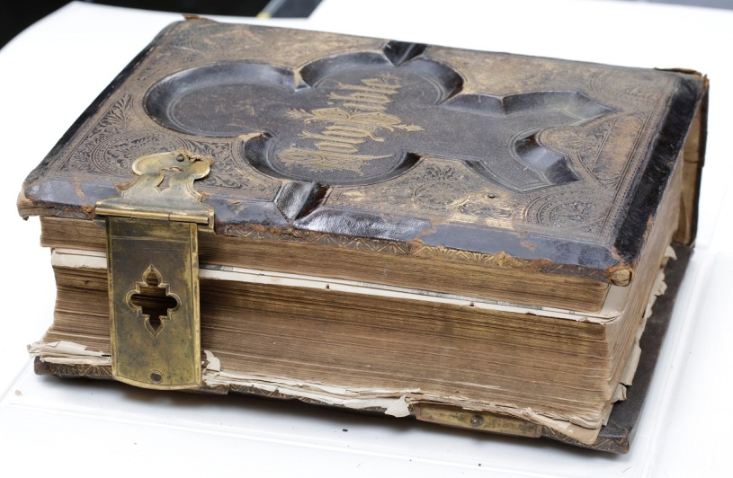 Shearer family illustrated bible with leather hardcover binding, and ornate metallic recessed design with metal clasp enclosures