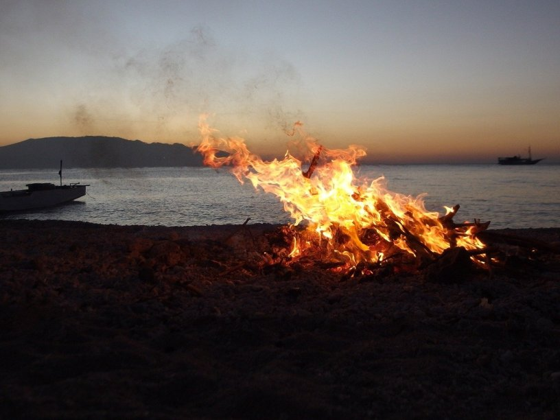 Image of a fire on a beach at dusk