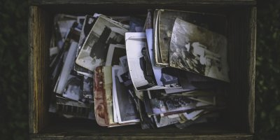 old photos piled in a wooden box